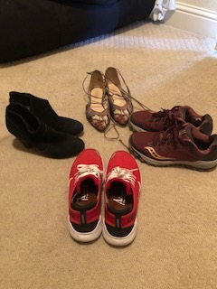 4 pairs of shoes on the floor. Black ankel booties at 9:00, red Nikes at 6:00, running shoes at 3:00, and colorful pointed toe flats at 12:00