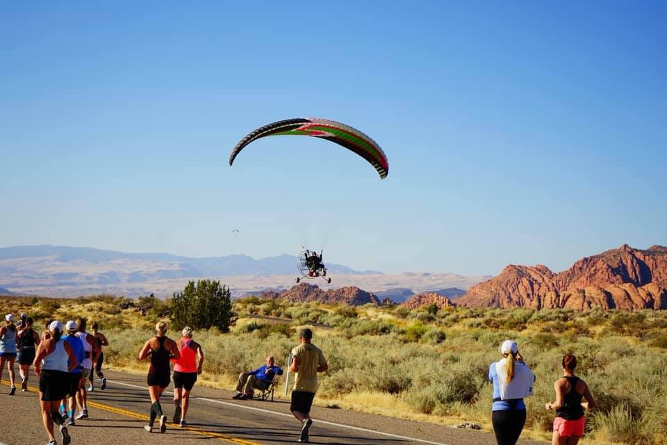 image of a hang glider floating above St. George Marathon runners